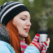 Winter woman drinking tea wearing warm winter - Stock Photo