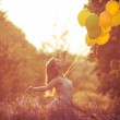 Young beautiful girl with baloons in the field of flowers — Stock Photo #26180097