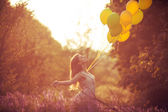 Young beautiful girl with baloons in the field of flowers — Stock Photo