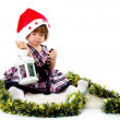 Little girl wearing a Santa hat and playing with baubles — Foto Stock