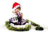 Little girl wearing a Santa hat and playing with baubles — Stock Photo