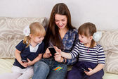 Three sisters with smartphones — Стоковое фото
