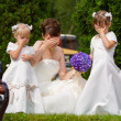 Bride stand with little girls in elegant dresses — Stock Photo
