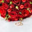 Wedding rings with a bouquet of roses — Stok fotoğraf