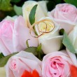 Wedding rings on a bouquet of roses — Stock Photo