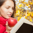 Charming girl with apple in the autumn park and reads book — Photo