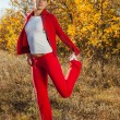 Young woman stretching before her run outdoors on a cold fall, winter day — Stock Photo