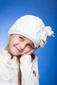 Portrait of an adorable baby girl wearing a knit white winter hat. — Stock Photo