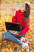 Beautiful girl with apple on yellow leaves with notebook — Stock Photo