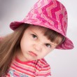Portrait of an angry baby girl in hat. — Stock Photo #23528371
