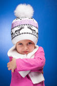 Portrait of an angry baby girl wearing a knit pink and white winter hat. — Stock Photo