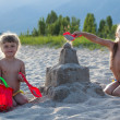 Stock Photo: Two girls building sandcastle