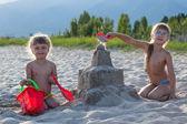 Twee meisjes sandcastle gebouw — Stockfoto