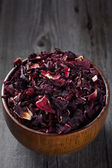 Heap of hibiscus tea in a wooden bowl on old board — Stock Photo