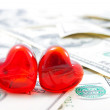 Two glass hearts on dollar background — Stock Photo