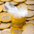Coins and feather — Stock Photo