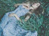 Beautiful lady lying amond flowers — Stock Photo