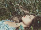 красивая леди лежа amond цветы — Стоковое фото