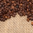 Coffee grains on rough fabric of linen close-up — Stock Photo