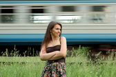 Portrait of young women against train — Stock Photo