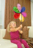 Baby girl with pinwheel sitting in sofa — Stock Photo