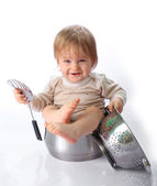 Baby boy in the kitchen pan — Stock Photo
