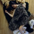 Young girl with several natural fur coats — 图库照片