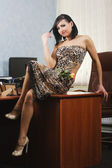 Young girl sitting on the office table — Stockfoto