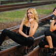 Beauty girl sitting on the railroad track — Stock Photo