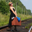 Girl on the railroad track with suitcase — Stock Photo