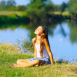 Little girl sitting by the river coastline in summer time — Stock Photo