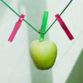 Green apple hanging on the rope with clothespins — Stock Photo