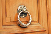 Ancient style carved knocker of the door — Stock Photo