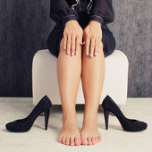 Legs of business woman sitting in black suit — Stock Photo
