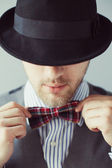 Portrait of a man in the black hat correcting his bow-tie — Stock Photo