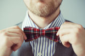 Fashion photo of a man with beard correcting his bowtie — Stock Photo