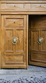 Opened door with ancient style carved knocker — Stock Photo