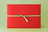 Red envelope with ribbon — Stock Photo