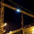 Building cranes at night - Stock Photo