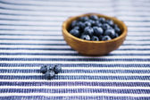 Blueberries on the wooden plate — Stock fotografie