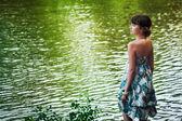 Girl staying by a lake — Foto de Stock