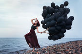 Beautiful girl walking with black balloons — Stockfoto