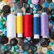 Buttons and spools of thread — Stock Photo
