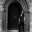 Young woman in a black dress against old stone gates outdoor shot — Stock Photo