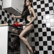 Sexy young model girl with a gorgeous figure posing in kitchen — Stock Photo #26678367