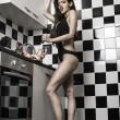 Sexy young model girl  with a gorgeous figure posing in kitchen — Stock Photo