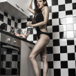 Sexy young model girl with a gorgeous figure posing in kitchen — Stock Photo #26678529