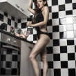 Stock Photo: Sexy young model girl with a gorgeous figure posing in kitchen