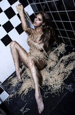 A beautiful young model lying on a floor playing eating with pasta, implied nudity — Stock Photo