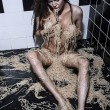 A beautiful young model lying on a floor playing eating with pasta, implied nudity — Stockfoto